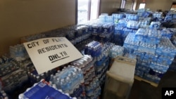 FILE - In this Friday, Feb. 5, 2016 file photo, hundreds of cases of bottled water are stored at a church in Flint, Michigan.
