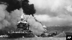 FILE - In this Dec. 7, 1941 file photo, part of the hull of the capsized USS Oklahoma is seen at right as the battleship USS West Virginia, center, begins to sink after suffering heavy damage, while the USS Maryland, left, is still afloat in Pearl Harbor, Oahu, Hawaii. A Navy seaman killed in the attack is being buried with full military honors nearly 75 years after the bombing.