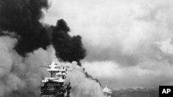 7 دسمبر 1941 میں امریکی بندرگاہ پرل ہاربر پر جاپانی طیاروں کے حملے کے بعد ایک بحری جہاز کو آگ لگی ہوئی ہے، (فائل فوٹو)