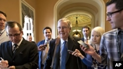 "Senate Minority Leader Mitch McConnell of Kentucky, center, arrives at his office in the Capitol as he and Senate Majority Leader Harry Reid of Neveda try to negotiate a legislative solution to avoid the so-called ""fiscal cliff"", Sunday, December 30, 2012."