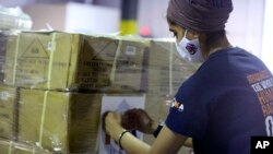 Dr. Abhu Kaur of Khalsa Aid USA, a global humanitarian organization, labels a pallet of electrical transformers, which will be shipped to New Delhi with oxygen concentrators this week on New York's Long Island, Friday, May 7, 2021. (AP Photo/Jessie Wardar