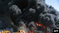 FILE - In this May 10, 2005 file photo, Beiji refinery workers attempt to extinguish a burning pipe line fire after militants set fire to Iraq's largest oil refinery in al-Fath, about 15 kilometer (10 miles) north of Beiji, Iraq. Gunmen attacked Saturday,