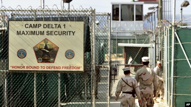 US military guards walk within Camp Delta military-run prison, at the Guantanamo Bay US Naval Base, Cuba, June 27, 2006.