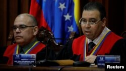 Juan Mendoza, right, Venezuela's Supreme Court second vice president and president of the Constitutional Chamber, seated next to Arcadio Delgado, a member of the of the Constitutional Chamber, gives a news conference in Caracas, Venezuela, July 21, 2017. The Supreme Court ruled that the National Assembly's appointment of a new slate of judges to the high court was unconstitutional.
