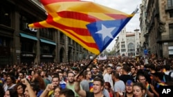 """Demonstrators with """"estelada,"""" or Catalonia independent flag, gather in protest in front of the Spanish police station in Barcelona, Spain, Oct. 3, 2017."""
