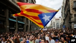 "FILE - Demonstrators with ""estelada,"" or the Catalonia independent flag, gather in protest in front of the Spanish police station in Barcelona, Spain, Oct. 3, 2017."