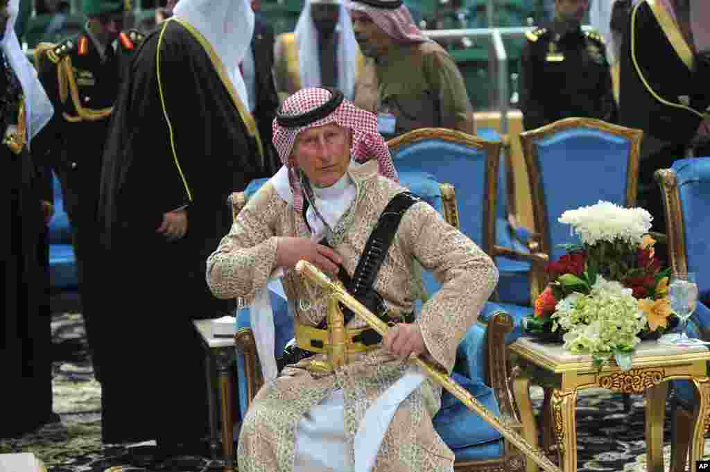 Britain's Prince Charles wears traditional Saudi clothes as he attends the traditional Saudi dancing best known as 'Arda', performed during Janadriya culture festival at Der'iya in Riyadh, Feb. 18, 2014.