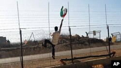 A protester holds a Palestinian flag in front of Israeli soldiers during a protest against the controversial Israeli barrier in the West Bank village of Bilin, near Ramallah, 26 Nov 2010