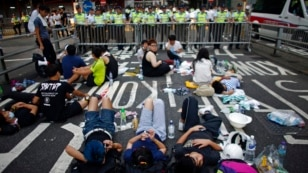 Protesters block a street near government headquarters in Hong Kong September 30, 2014. Tens of thousands of pro-democracy protesters extended a blockade of Hong Kong streets on Tuesday, stockpiling supplies and erecting makeshift barricades ahead of what