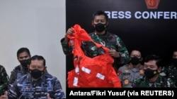 Seorang personel militer memegang escape suit yang diyakini berasal dari kapal selam TNI AL KRI Nanggala-402 yang tenggelam saat jumpa pers di Bandara I Gusti Ngurah Rai, Bali, 25 April 2021. (Foto: Antara/Fikri Yusuf via REUTERS)