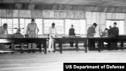UN delegate Lt. Gen. William K. Harrison, Jr. (seated left), and Korean People's Army and Chinese People's Volunteers delegate Gen. Nam Il (seated right) sign the Korean War armistice agreement at Panmunjom, Korea, July 27, 1953.