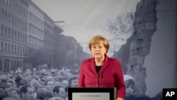 FILE - German Chancellor Angela Merkel speaks near a photograph of the former Berlin Wall, which had separated Germany's west and Communist east for decades until late 1989. The country's ruling coalition agreed to increase pensions for former East Germans.