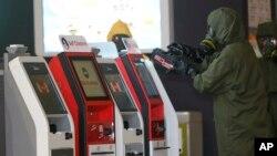 Petugas berseragam dari tim 'hazmat' atau bahan berbahaya memindai mesin-mesin di bandar udara internasional Kuala Lumpur (26/2). (AP/Daniel Chan)
