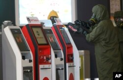A hazmat crew scana the check-in kiosk machines at Kuala Lumpur International Airport 2 in Sepang, Malaysia, Feb. 26, 2017.