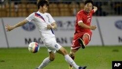 중국 톈진에서 제6회 동아시아경기대회가 열리는 가운데, 10일 벌어진 남북한 남자 축구 경기에서 북한의 리혁철(오른쪽)이 한국 최영광 옆으로 슛을 날리고 있다.