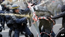 Policías antidisturbios luchan con manifestantes que piden un acuerdo para detener el cambio climático, en la Plaza de la República en París, un día antes de la Cumbre del Clima de la ONU.