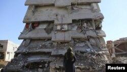 Seorang wanita melihat sebuah bangunan, yang rusak selama operasi keamanan dan bentrokan antara pasukan keamanan Turki dan militan Kurdi, di kota tenggara Cizre di provinsi Sirnak, Turki, 2 Maret 2016. (Foto: Reuters)