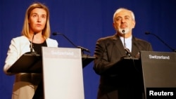 European Union foreign policy chief Federica Mogherini, left, issues a statement with Iran's Foreign Minister Mohammad Javad Zarif in Lausanne, Switzerland, April 2, 2015.