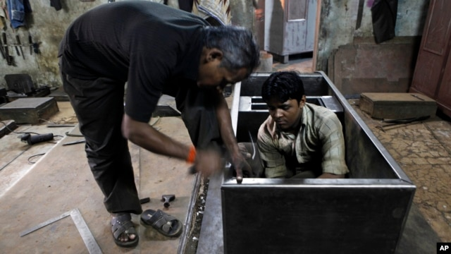 An Indian worker hammers on a steel cupboard at a metal wardrobe factory in Mumbai, India, Oct. 12, 2012.
