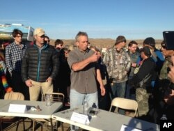 FILE - Robert F. Kennedy Jr., center, an environmental attorney and president of the New York-based Waterkeeper Alliance, speaks with opponents of the Dakota Access oil pipeline at the main protest camp, Nov. 15, 2016, near Cannon Ball, North Dakota.