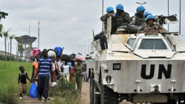 Inhabitants of the Abobo district in Abidjan flee the area past a United Nations armored vehicle following fresh clashes between forces loyal to rival claimants for the presidency on February 27, 2011
