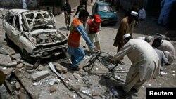 ພວກກູ້ໄພ ແລະເຈົ້າໜ້າທີ່ຮັກສາຄວາມປອດໄພເກັບກໍາເອົາ ຫລັກຖານຢູ່ນອກຫ້ອງການຫາສຽງເລືອກຕັ້ງຂອງທ່ານ Haji Nasir Khan Afridi ທີ່ຖືກທໍາລາຍໂດຍລະເບີດແຕກ ໃນເມືອງ Peshawar ໃນວັນທີ 28 ເມສາ 2013.