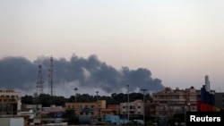 Black smoke rises from the vicinity of the University of Benghazi where clashes are taking place between pro-government forces and Islamist militias in Benghazi, Oct. 18, 2014.