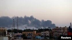 Asap mengepul di sekitar Universitas Benghazi di mana terjadi bentrokan milisi dan pasukan pro-pemerintah (18/10).