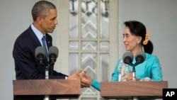 U.S. President Barack Obama, left, and Myanmar's opposition leader Aung San Suu Kyi shake hands during a news conference at her home in Yangon, Myanmar, Nov. 14, 2014.