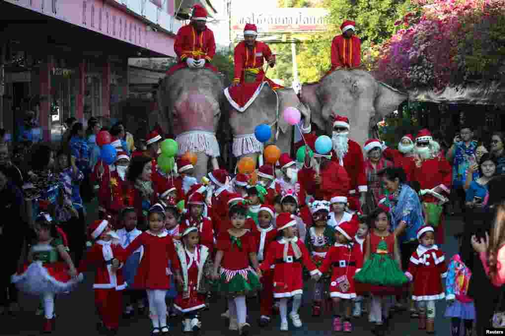 2017年12月22日,泰国大城府的Jirasart学校圣诞节庆祝活动期间,穿着圣诞老人服装的老师和学生以及大象(Elephant)游行。