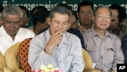 Cambodia's Prime Minister Hun Sen, center, smokes as he sits with Interior Minister Sar Kheng, left, and former Finance Minister Keat Chhun, right, during the inauguration of the China-funded construction of a bridge in Mouk Kampoul district, Kandal province, file photo.