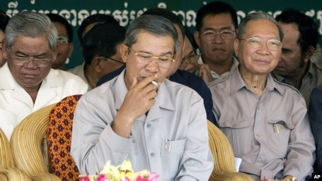 Cambodia's Prime Minister Hun Sen, center, smokes as he sits with Interior Minister Sar Kheng, left, and Finance Minister Keat Chhun, right, during the inauguration of the China-funded construction of a bridge in Mouk Kampoul district, Kandal province, some 20 kilometers (12 miles) north of Phnom Pen, Cambodia, file photo.