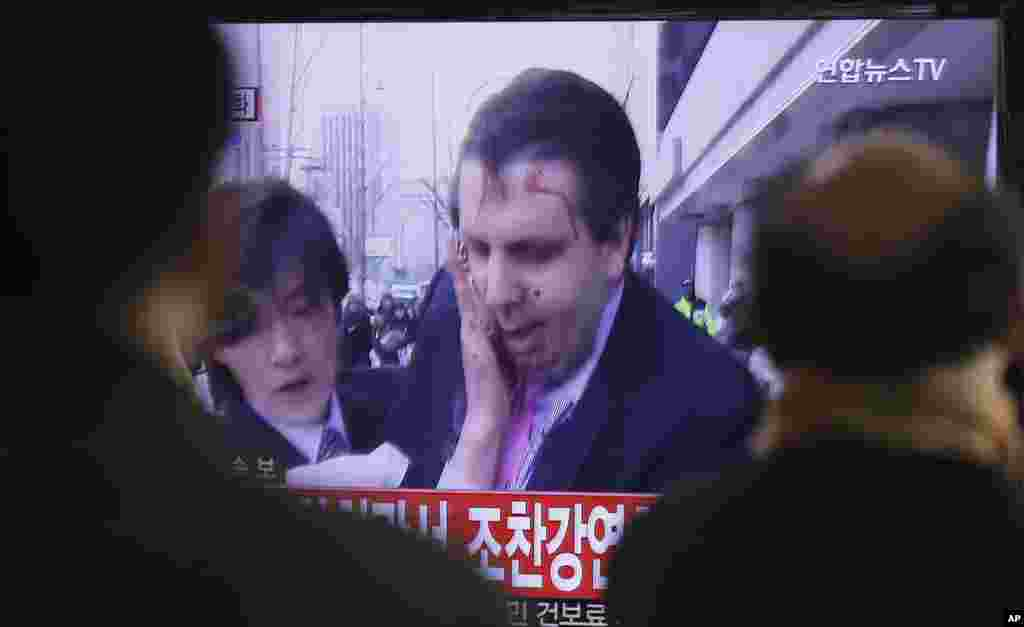 South Korean men watch a TV news program reporting that U.S. Ambassador to South Korea Mark Lippert was injured in a knife attack at a railway station in Seoul, South Korea, March 5, 2015.
