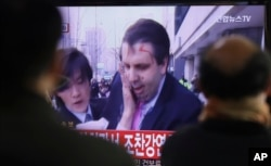 FILE - South Korean men watch a TV news program reporting U.S. Ambassador to South Korea Mark Lippert injured in a knife attack at Seoul railway station in Seoul, South Korea, March 5, 2015.