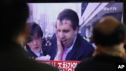 South Korean men watch a TV news program reporting U.S. Ambassador to South Korea Mark Lippert injured in a knife attack at Seoul railway station in Seoul, South Korea, Thursday, March 5, 2015. Lippert was slashed on the face and wrist by a man wielding a