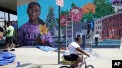 Un niño monta su bicicleta el lunes 29 de julio de 2019 después de ofrecerse como voluntario para pintar un mural afuera de la Iglesia de la Comunidad New Song en la sección Sandtown de Baltimore. (Foto AP / Julio Cortez)