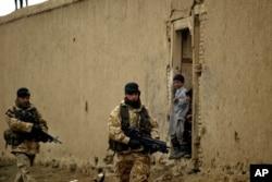 Arhiva - Britanski vojnici iz međunarodne koalicije predvođene NATO-om patroliraju dok ih afganistanska djeca posmatraju u Kabulu, Afganistan, 27. januara 2006.