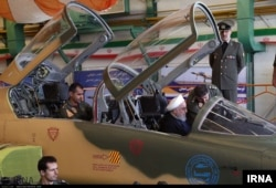 Iranian President Hassan Rouhani inspects the cockpit of what Iran calls its new domestically designed Kowsar fighter jet, Aug. 21, 2018.
