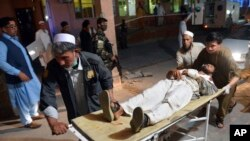 FILE - A wounded man is brought by stretcher into a hospital in Jalalabad city, capital of Nangarhar province, east of Kabul, June 16, 2018.