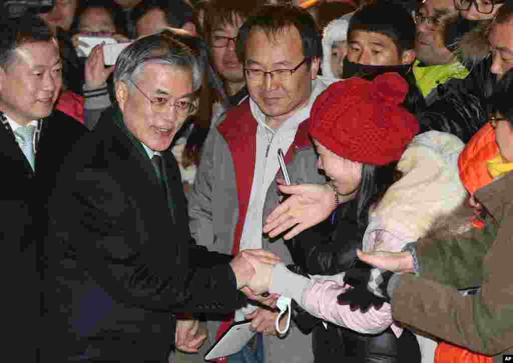 South Korean opposition Democratic United Party's presidential candidate Moon Jae-in, second from left, shakes hands with supporters after he cast his ballot in the presidential election in Seoul, Dec. 19, 2012.
