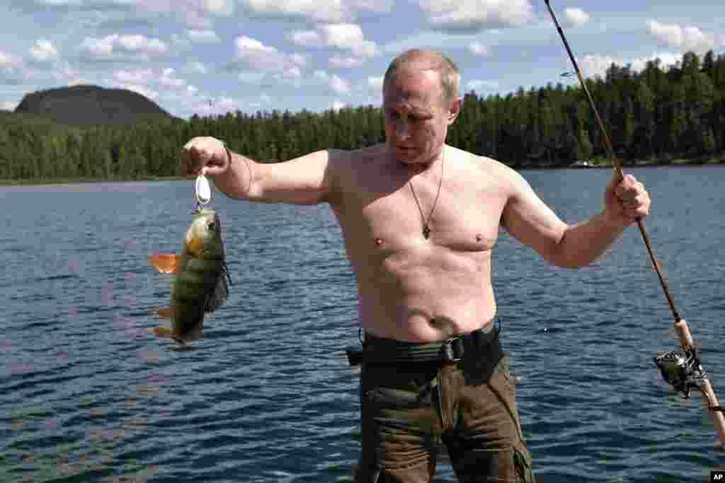 克里姆林宫新闻室2017年8月5日发布的照片显示,俄罗斯总统弗拉基米尔·普京在西伯利亚泰瓦地区小做休息,钓到大鱼。