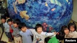 """Niños japoneses sostienen un """"planeta feliz"""" hecho de Shibori-zome, un método tradicional japones."""