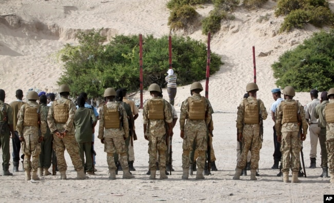 FILE - Hassan Hanafi Haji, center, a former journalist accused of belonging to al-Shabab and involvement in the killings of five Somali journalists, is tied to a wooden post as he is prepared to be executed by firing squad in the capital Mogadishu, Somalia, April 11, 2016.