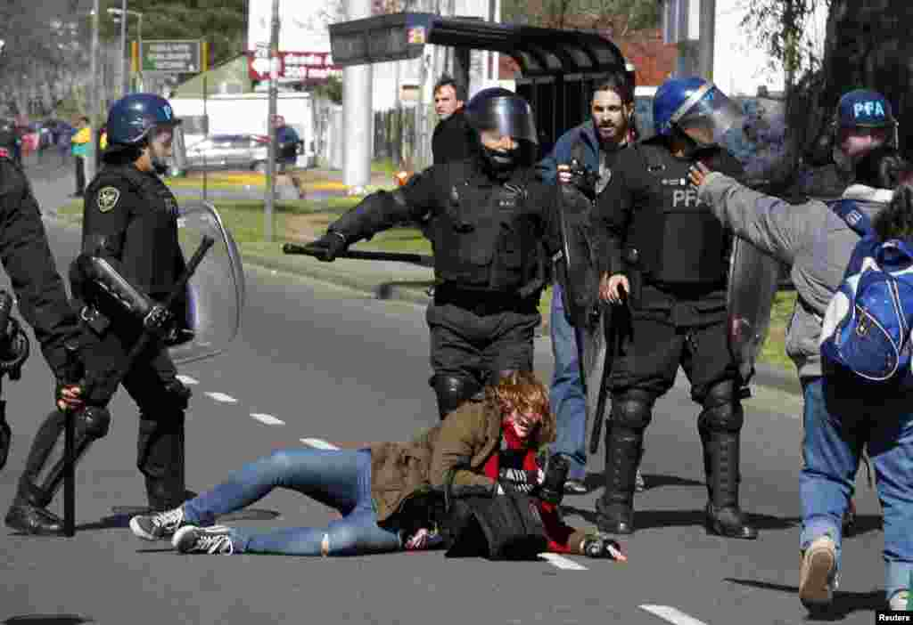 Photographer Maria Pirsch falls on the road after being hit by anti-riot policemen during a protest staged by state workers who were seeking to block a road in Buenos Aires, Argentina. Opposition labor unions have planned a 24-hour strike across the country on Aug. 28, 2014, to press President Cristina Fernandez de Kirchner's administration for wage increases in line with inflation rate and to reduce the tax income in salaries.