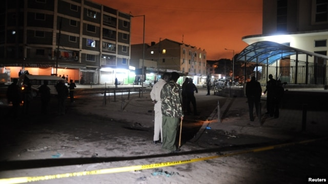 Policemen inspect the secured section at the scene of the blast in Eastleigh suburb of Kenya's capital Nairobi, December 7, 2012.
