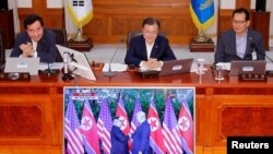 문재인 한국 대통령이 12일 청와대 내각 회의 중 미북정상회담 실시간 생중계를 보고 있다.