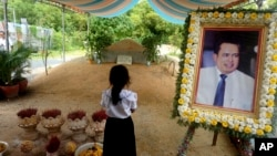 In this Nov. 20, 2016 photo, a girl stands by a portrait of Kem Ley, a Cambodian prominent political analyst, at his grave in Ang Takok, Cambodia. Kem Ley, a poor rice farmer's son turned champion of Cambodia's have-nots, was sipping his usual iced latte in the same chair he had occupied most mornings for years when a former soldier he may never have met walked into the Caltex gas station cafe. Armed with a semi-automatic Glock pistol, the assassin fired into his chest and head, execution-style. Then he walked casually away from the scene. (AP Photo/Denis Gray)