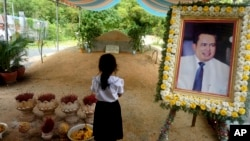 In this Nov. 20, 2016 photo, a girl stands by a portrait of Kem Ley, a Cambodian prominent political analyst, at his grave in Ang Takok, Cambodia. Kem Ley, a poor rice farmer's son turned champion of Cambodia's have-nots, was sipping his usual iced latte in the same chair he had occupied most mornings for years when a former solider he may never have met walked into the Caltex gas station cafe. Armed with a semi-automatic Glock pistol, the assassin fired into his chest and head, execution-style. Then he walked casually away from the scene. (AP Photo/Denis Gray)