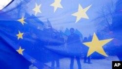 Les militants pro Union européenne sont vus à travers un drapeau de l'UE lors d'un rassemblement en face du bâtiment du ministère ukrainien de l'Intérieur à Kiev , en Ukraine , le 17 décembre 2013.