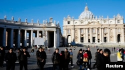 People walk in St. Peter's Square at the Vatican, February 19, 2013.